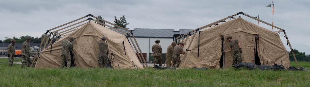 Airmen assemble tents.