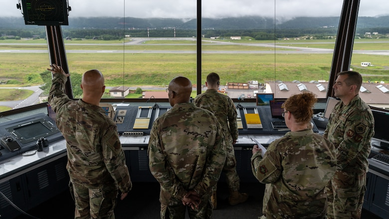 Airmen look at the flightline from the Air Traffic Control Tower