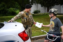 Senior Airman Carlos Howard, 66th Security Forces Squadron Positive Policing program lead, presents a Blue Bucks certificate to Parker Jones, Hanscom resident, for wearing a helmet while riding a bike at Hanscom Air Force Base, Mass., July 13. The Positive Policing program allows 66 SFS defenders to recognize community members for adhering to safety protocols or traffic laws. (U.S. Air Force photo by Lauren Russell)