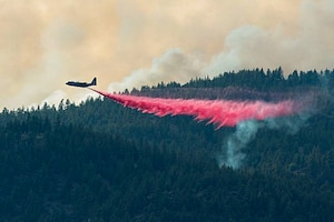 Air National Guard C-130 drops retardant on the Beckwourth Complex Fire July 9, 2021 near Frenchman Lake in N. California