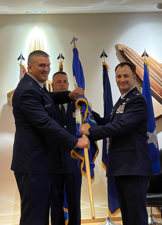 Col. Matthew Jones, former 101st Air and Space Operations Group (AOG) commander, passes the ceremonial flag to Brig. Gen. Michael Valle, Florida National Guard Assistant Adjutant General (Air), and Florida Air National Guard commander, during an AOG change of command, Tyndall Air Force Base, July 14, 2021.