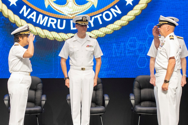 U.S. Navy Capt. Nimfa Teneza-Mora, outgoing commander of Naval Medical Research Unit Dayton, left, passes command to Capt. Walt Dalitsch, incoming commander of NAMRU-D, right, as  Capt. William Deniston, commander of Naval Medical Research Center, center, presides during the unit's change of command ceremony, July 9, 2021, at Wright Patterson Air Force Base, Ohio. NAMRU-Dayton is one the premier research facilities in the Navy and the unit has contributed significantly to understanding health, safety, and performance consequences of flight on humans. (U.S. Air Force photo by Wesley Farnsworth)