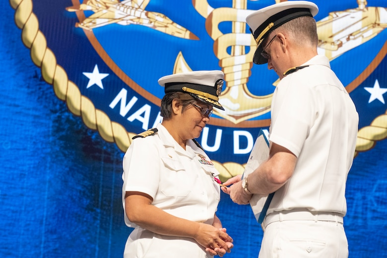 U.S. Navy Rear Admiral Tim Weber, commander of Naval Medical Forces Pacific, presents Capt. Nimfa Teneza-Mora, outgoing commander of Naval Medical Research Unit Dayton, with her Legion of Merit award, the unit's change of command ceremony, July 9, 2021, at Wright Patterson Air Force Base, Ohio. NAMRU-Dayton is one the premier research facilities in the Navy and the unit has contributed significantly to understanding health, safety, and performance consequences of flight on humans. (U.S. Air Force photo by Wesley Farnsworth)