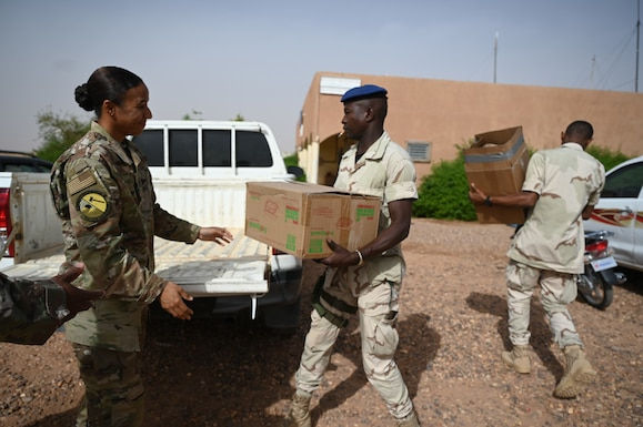 U.S. Air Force Staff Sgt. Brianna N. Creveling, 435th Air Expeditionary Wing Chaplain Corps religious affairs non-commissioned officer in charge, donates supplies to members from the Nigerien Armed Forces at Nigerien Air Base 201, Agadez, July 8, 2021.