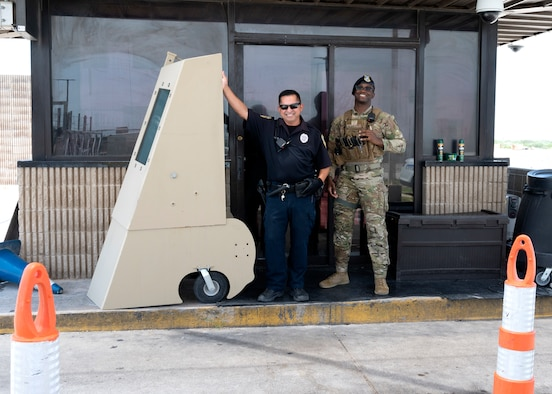 Security Forces personnel at the west gate pose for a photo behind a barrier at Laughlin Air Force Base, July 15, 2021. The Security Forces Personel will be changing the point of entry on July 17, 2021, to allow for upgrades to be completed to the west gate. (U.S. Air Force Photo by Senior Airman Nicholas Larsen)
