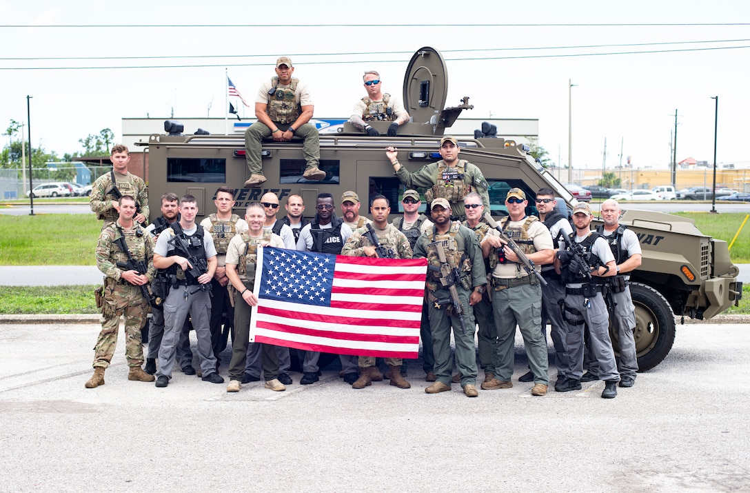 Members from the 325th Security Forces Squadron tactical response team and Bay County Sheriff's Office and Panama City Police Department special weapons and tactics teams pose for a photo in Panama City, Florida, July 13, 2021. The three agencies trained together to share tactics and experience from both military and civilian police careers in order to become more well-rounded units. (U.S. Air Force photo by Staff Sgt. Stefan Alvarez)