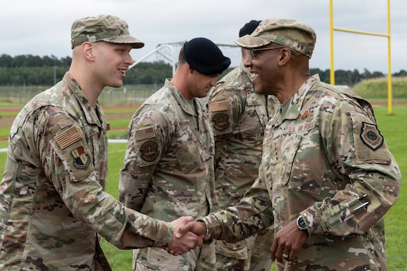 U.S. Air Force Chief of Staff Gen. CQ Brown Jr. (right) presents a challenge coin to U.S. Air Force Tech. Sgt. Kyle Weik, 52nd Munitions Maintenance Group chief inspector of quality assurance, July 16, 2021, on Spangdahlem Air Base, Germany.