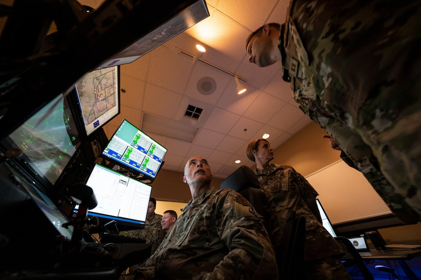 Lt. Gen. Robert Miller, Surgeon General of the Air Force and Space Force, looks at a flight instructor from the pilot's seat in an  MQ-9 Reaper simulator.