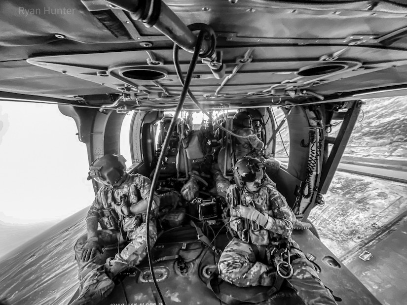 Staff Sgt. Stephen Parker and Staff Sgt. Shaun Morris, along with pilots, Capt. Jonathan Strayer and Chief Warrant Officer Kristan Beard, conduct hoist and joint MEDEVAC training with U.S. Marines over New Antonik, Afghanistan July 2020.