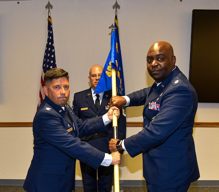 Lt. Col. Costau C. Bastien (right), commander, 403rd Force Support Squadron accepts the 403rd Force Support Squadron guidon from Col. Reggie Trujillo (left), commander, 403rd Mission Support Group during an assumption of command ceremony in the Sablich Center auditorium at Keesler Air Force Base, Miss. July 10, 2021. (U.S. Air Force photo by Tech. Sgt. Michael Farrar)