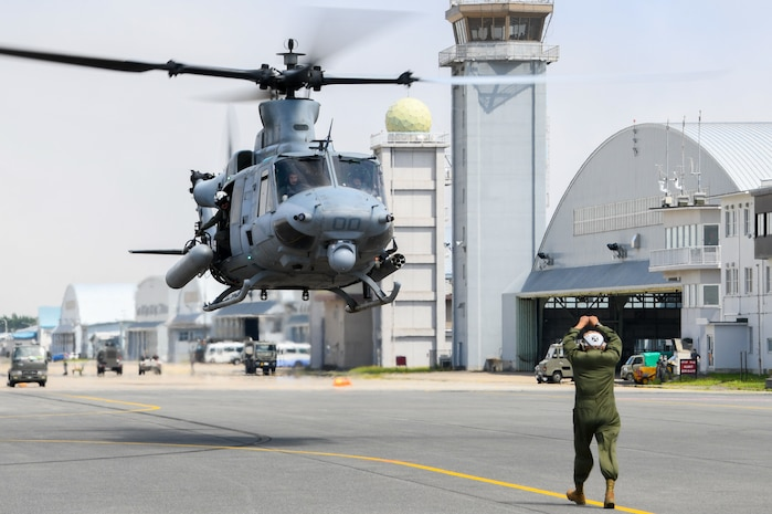 """MISAWA, Japan (July 15, 2021) – Staff Sgt. Gustavo Lopez, a Plane Captain assigned to the """"Vipers"""" of Marine Light Attack Helicopter Squadron (HMLA) 169, guides an UH-1Y Venom as it arrives at Naval Air Facility (NAF) Misawa. HMLA-169 is at NAF Misawa to conduct Tilt Rotor/Rotary Wing (TR-RW) training exercises and reduce the training activity impact on Okinawa."""