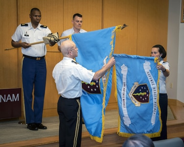 Army Lt. Gen. Ronald J. Place, director of the Defense Health Agency, unfurls the DHA flag