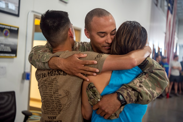 Senior Airman Laurence Pierre, 921st Contingency Response Squadron defender, hugs friends after arriving to the Global Reach Deployment Center June 19, 2021, at Travis Air Force Base, California. Devil Raiders supported retrograde operations in the Central Command area of responsibility as part of Task Force 74. (U.S. Air Force photo by Master Sgt. David W. Carbajal)