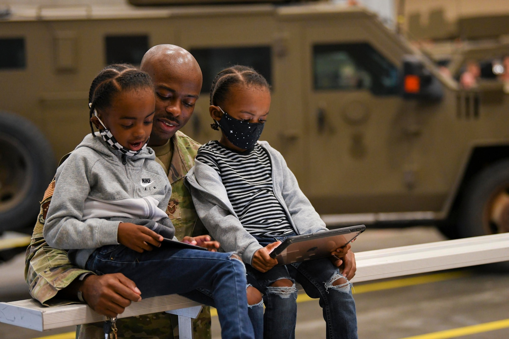An airman stands behind two seated children looking at tablets.