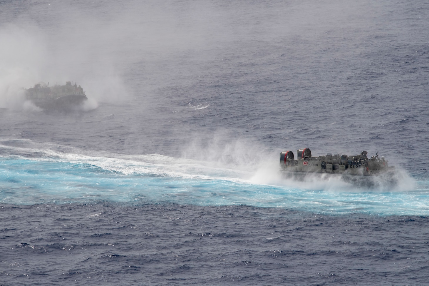PHILIPPINE SEA (June 13, 2021) Two landing craft, air cushion from the Japan Maritime Self Defense Force sail alongside the America Amphibious Ready Group (ARG) during bilateral operations. The America ARG, along with the 31st Marine Expeditionary Unit, is operating in the U.S. 7th Fleet area of operations to enhance interoperability with allies and partners and serve as a ready response force to defend peace and stability in the Indo-Pacific region.
