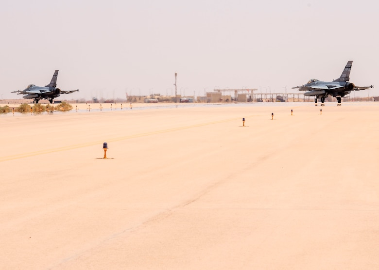 Two U.S. Air Force F-16 Fighting Falcons taxi on a runway at Prince Sultan Air Base, Kingdom of Saudi Arabia, while preparing to take part in a counter unmanned aerial system integration mission with joint and Royal Saudi aircraft, June 30, 2021. U.S. Air Forces Central aircraft regularly work with coalition and partner nations to test their collective counter-UAS capabilities to ensure the security and stability of regional airspace.  (U.S. Air Force photo by Technical Sgt. Veronica Woodward)