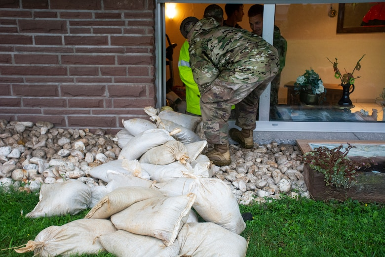 U.S. Air Force members from the 52nd Civil Engineer Squadron from Spangdahlem Air Base, Germany, work with German first responders and community members to deliver sandbags to the town of Binsfeld, Germany, July 14, 2021.