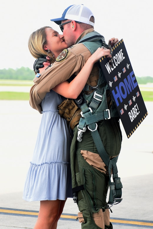 """U.S. Air Force Capt. Kaleb Nypaver, a 157th Fighter Squadron pilot, greets his loved one at McEntire Joint National Guard Base, South Carolina, after returning from a deployment to Prince Sultan Air Base, Kingdom of Saudi Arabia, July 16, 2021. """"Swamp Fox"""" Airmen from the South Carolina Air National Guard's 169th Fighter Wing were deployed to PSAB for the past three months to project combat power and help bolster defensive capabilities against potential threats in the region. (U.S. Air National Guard photo by Senior Airman Mackenzie Bacalzo, 169th Fighter Wing Public Affairs)"""