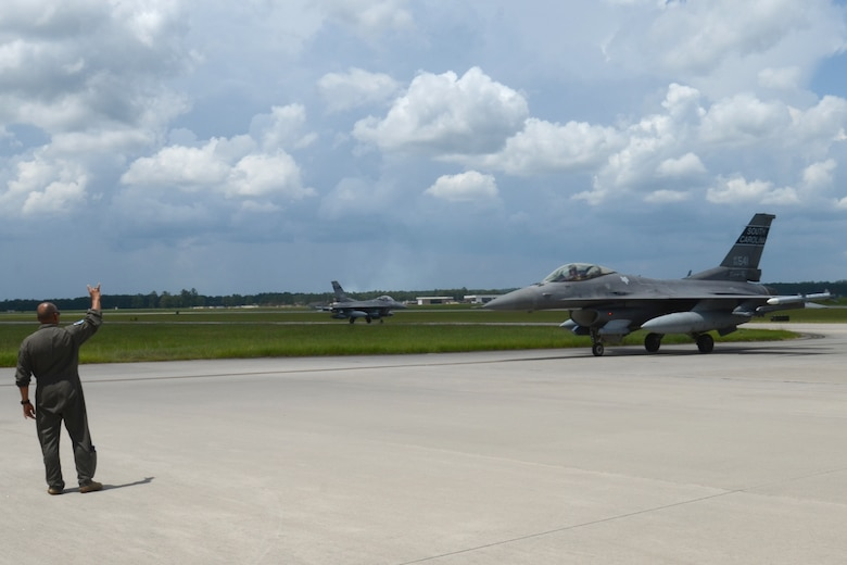 """U.S. Air Force Col. Akshai Gandhi, 169th Fighter Wing commander, gives the """"Swamp Fox"""" hand signal to a F-16 fighter jet pilot returning home July 16, 2021 to McEntire Joint National Guard Base, South Carolina.  U.S. Air Force personnel from the 169th Fighter Wing recently deployed to Prince Sultan Air Base, Kingdom of Saudi Arabia. """"Swamp Fox"""" Airmen from the South Carolina Air National Guard's 169th Fighter Wing have been deployed to PSAB for the past three months to project combat power and help bolster defensive capabilities against potential threats in the region. (U.S. Air National Guard photo by Lt. Col. Jim St.Clair, 169th Fighter Wing Public Affairs)"""