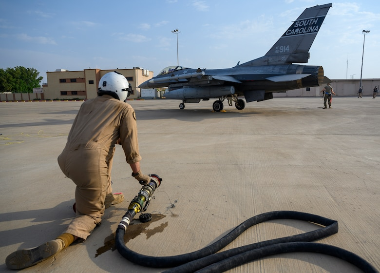 """A U.S. Marine with Marine Aerial Refueler Transport Squadron 352, assigned to Special Purpose Marine Air-Ground Task Force – Crisis Response – Central Command, prepares to conduct a """"hot pit"""" aircraft-to-aircraft refueling of a U.S. Air Force F-16 Fighting Falcon during a counter unmanned aerial system integration mission with joint and Royal Saudi aircraft at a forward location in the Kingdom of Saudi Arabia, June 30, 2021. U.S. Air Forces Central aircraft regularly work with coalition and partner nations to test their collective counter-UAS capabilities to ensure the security and stability of regional airspace. (U.S. Air Force photo by Senior Airman Samuel Earick)"""