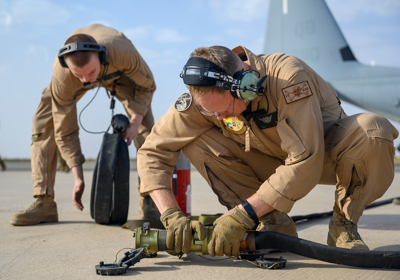 """U.S. Marines with Marine Aerial Refueler Transport Squadron 352, assigned to Special Purpose Marine Air-Ground Task Force – Crisis Response – Central Command, connect a fuel hose for a """"hot pit"""" aircraft-to-aircraft refueling during a counter unmanned aerial system integration mission with joint and Royal Saudi aircraft at a forward location in the Kingdom of Saudi Arabia, June 30, 2021. U.S. Air Forces Central aircraft regularly work with coalition and partner nations to test their collective counter-UAS capabilities to ensure the security and stability of regional airspace. (U.S. Air Force photo by Senior Airman Samuel Earick)"""