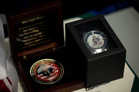 picture of an award certificate, a customized watch and a top performance coin.