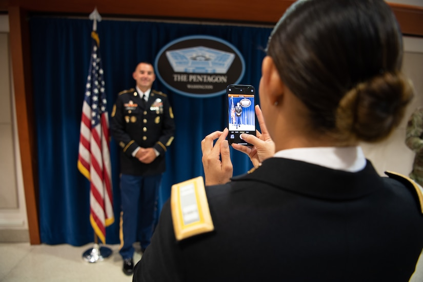 a woman takes a photo with her cell phone of a man in an army uniform.