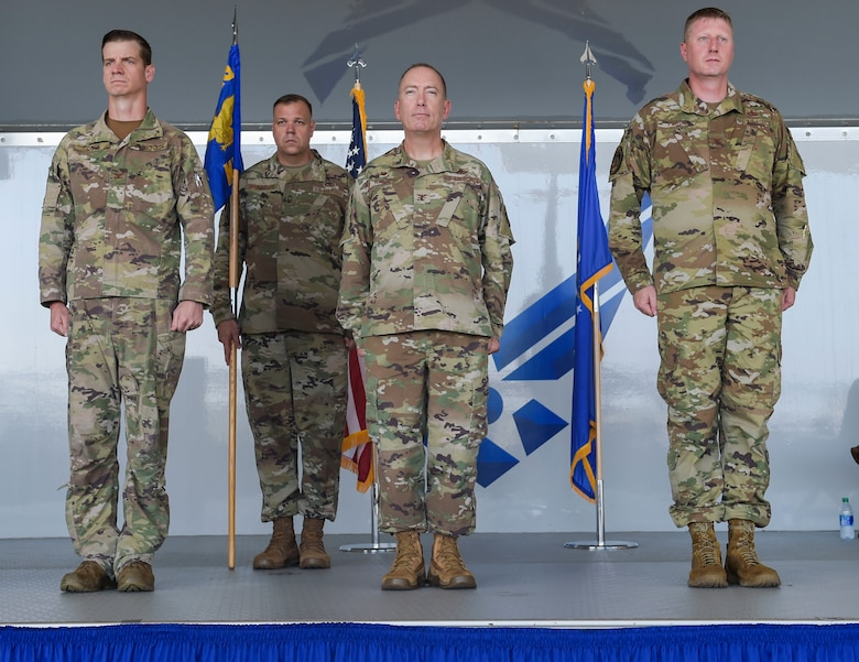 four men standing at attention in uniform