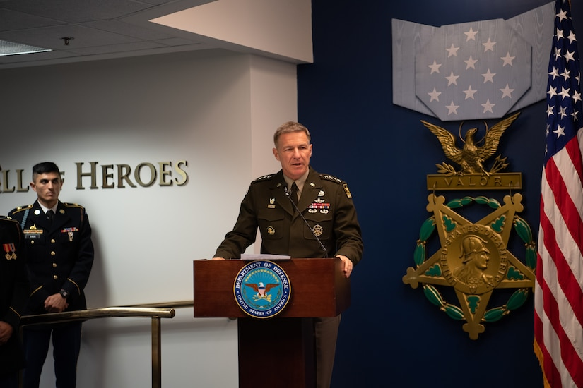 Man stands behind a podium on a stage wearing an army uniform.