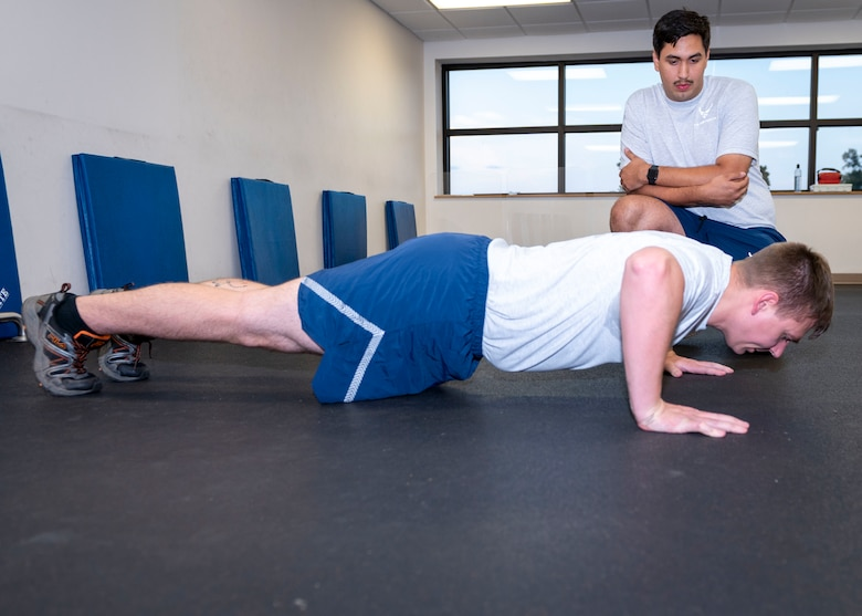 Tech. Sgt. Daniel Parker, 4th Equipment Maintenance Squadron phase and avionics NCO in charge and dock chief, performs push-ups while Senior Airman Kevin McMahon, 333rd Fighter Squadron weapons load crew member, counts his repetitions at Seymour Johnson Air Force Base, North Carolina, July 15, 2021.