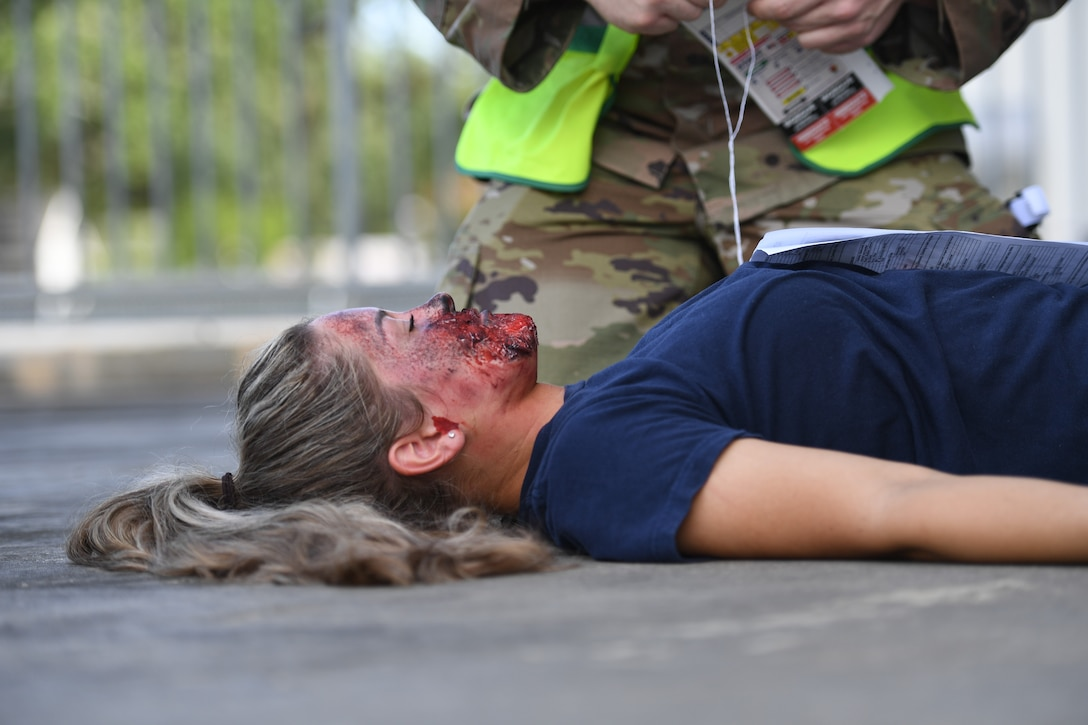 U.S. Air Force Airman Kelsey Wozniak, 81st Medical Support Squadron medical technician student, portrays an injured victim during an 81st Medical Group functional exercise behind the Keesler Medical Center at Keesler Air Force Base, Mississippi, July 15, 2021. The scenario involved a chlorine cylinder explosion causing chemical burns and other injuries on several victims. The mass casualty exercise was held to prepare for real-world events by strengthening disaster medical response capabilities. (U.S. Air Force photo by Kemberly Groue)