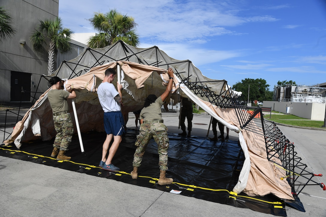 Members of the 81st Medical Group assemble a decontamination tent during an 81st MDG functional exercise behind the Keesler Medical Center at Keesler Air Force Base, Mississippi, July 15, 2021. The scenario involved a chlorine cylinder explosion causing chemical burns and other injuries on several victims. The mass casualty exercise was held to prepare for real-world events by strengthening disaster medical response capabilities. (U.S. Air Force photo by Kemberly Groue)