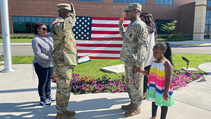 Solider reenlists while coworkers and family look on