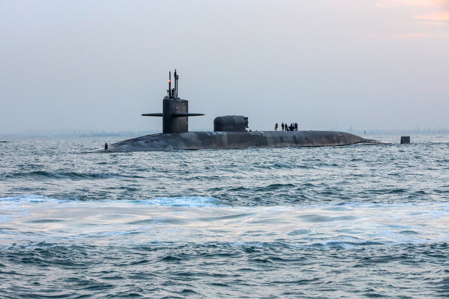 The guided-missile submarine USS Georgia (SSGN 729) transits the Gulf of Bahrain, outbound from a sustainment and logistics visit in Manama, Bahrain, Dec. 27, 2021.