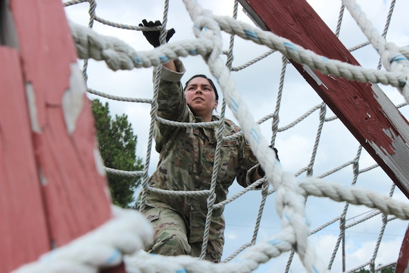 woman climbing obstacle course cargo net