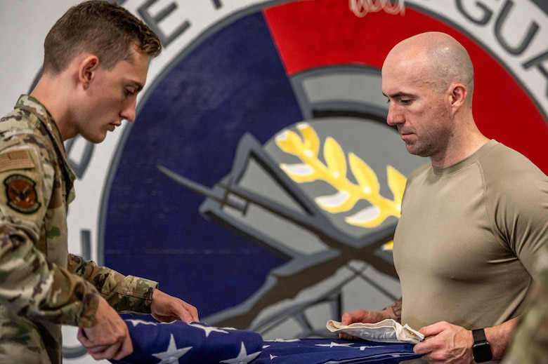 U.S. Air Force Airman 1st Class Christopher Wagner, 375th Logistics Readiness Squadron air transportation apprentice, and Master Sgt. Robert Van Buren, 113th Air Support Operations Squadron first sergeant, and folds a flag on Scott Air Force Base, Illinois, July 9, 2021. The ceremonial guardsmen will go back to their units with increased knowledge and train their wingmen on what they learned from USAF Honor Guard. (U.S. Air Force Photo by Airman 1st Class Isaac Olivera)