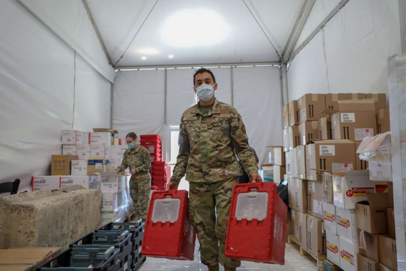"""Air Force Senior Airman David Espinal, right, a Bloomfield, New Jersey native and a logistical planner assigned to the 335th Air Expeditionary Group, exchanges the hazmat containers while U.S. Air Force Senior Airman Whitney Fenninger-Stutzman, left, inventories the medical supplies at the federally-run pilot Community Vaccination Center at the Greenbelt Metro Station in Greenbelt, Maryland, May 13, 2021. Deliveries of medical supplies such as these are made possible by the Defense Logistics Agency Troop Support Medical's Medical Surgical Prime Vendor program, named """"Best in Class"""" by the Office of Management and Budget in July 2021."""
