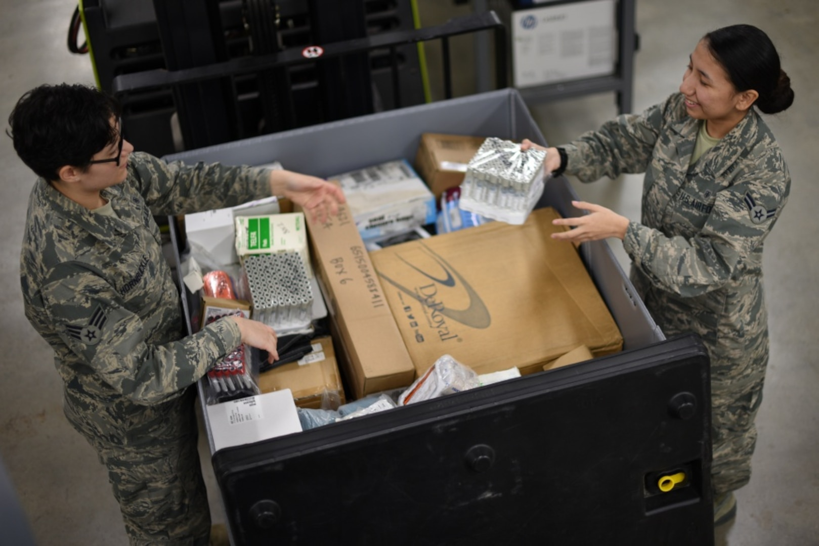 """Senior Airman Raina Hornbuckle, 22nd Medical Support Squadron medical logistician journeyman, and Airman 1st Class Ariana Vega, 22nd Medical Group medical logistician apprentice, look through medical supplies at McConnell Air Force Base, Kan., March 11, 2019. Thousands of deliveries like this each year are made possible by the Defense Logistics Agency Troop Support Medical's Medical Surgical Prime Vendor program named """"Best in Class"""" by the Office of Management and Budget in July 2021."""