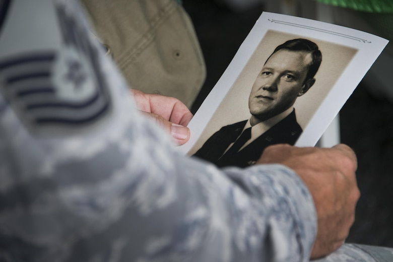 Airman holds old photo of .former commander.