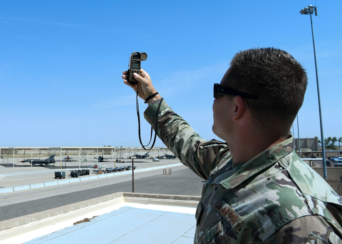 Staff Sgt. Craig Cassell, 56th Operations Support Squadron weather flight shift supervisor, measures the wind speed June 15, 2021, at Luke Air Force Base, Arizona.