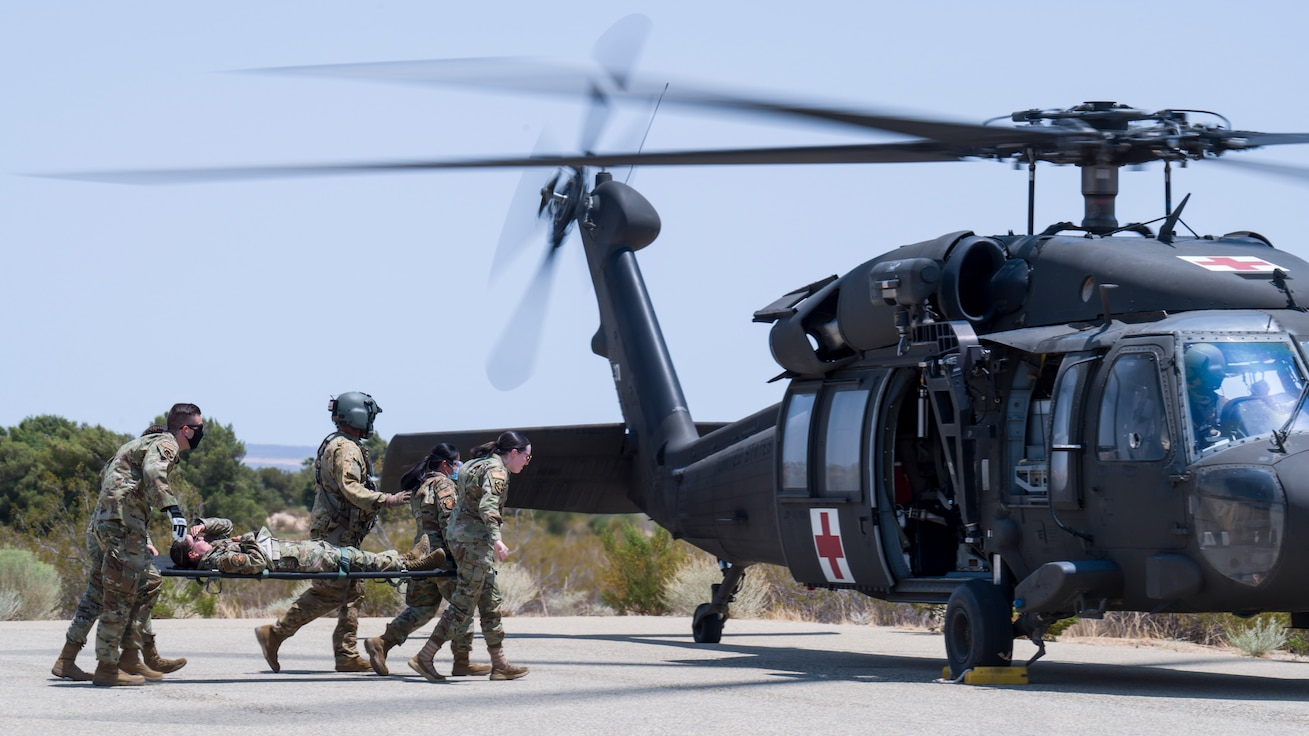 """412th Medical Group personnel approach a UH-60 Blackhawk helicoper during a training session at Edwards Air Force Base, California, July 15. Soldiers from C Company, """"Desert Dustoff,"""" 2916th Aviation Battalion, 916th Support Brigade, out of Fort Irwin, provided the training to the Edwards AFB Airmen. (Air Force photo by Giancarlo Casem)"""