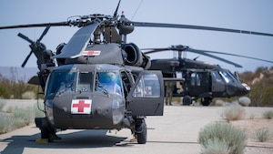 """Two UH-60 Blackhawks from C Company, """"Desert Dustoff,"""" 2916th Aviation Battalion, 916th Support Brigade, out of Fort Irwin, prepare to depart from the base clinic's helipad following air medevac training at Edwards Air Force Base, California, July 15. Team Edwards medical personnel were trained on proper patient loading procedures and were then given familiarization flights around the medical facility. (Air Force photo by Giancarlo Casem)"""