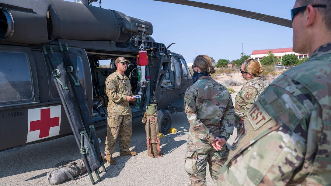 """Staff Sgt. Deric Randol, a flight medic with C Company, """"Desert Dustoff,"""" 2916th Aviation Battalion, 916th Support Brigade, out of Fort Irwin, trains members of the 412th Medical Group on proper patient loading procedures during a training session at Edwards Air Force Base, California, July 15. (Air Force photo by Giancarlo Casem)"""
