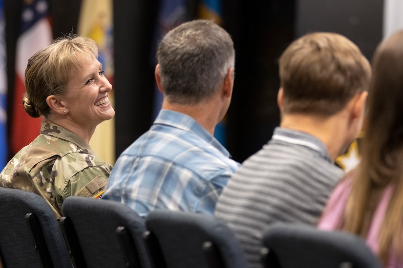 Col. Paige M. Jennings, U.S. Army Financial Management Command commander, is all smiles as she looks at her husband, Larry Jennings, during a ceremony at the Maj. Gen. Emmett J. Bean Federal Center in Indianapolis July 15, 2021. During his remarks, Gen. Edward M. Daly, U.S. Army Materiel Command commanding general, noted that the Jennings 28th wedding anniversary was two days after the assumption of command ceremony. (U.S. Army photo by Mark R. W. Orders-Woempner)