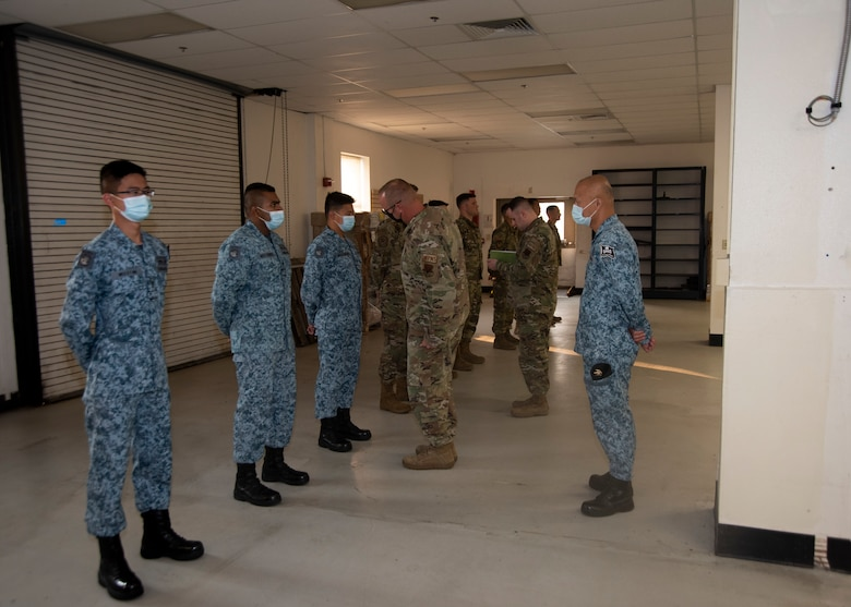 The Airmen from the United States Air Force and the Republic of Singapore Airmen get their uniforms inspected before the Quarterly Load Crew Competition begins.