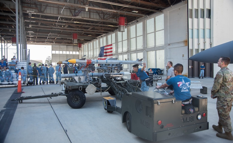 Republic of Singapore Air Force Airmen work together to load an Air Intercept Missile-9X on a jammer vehicle.