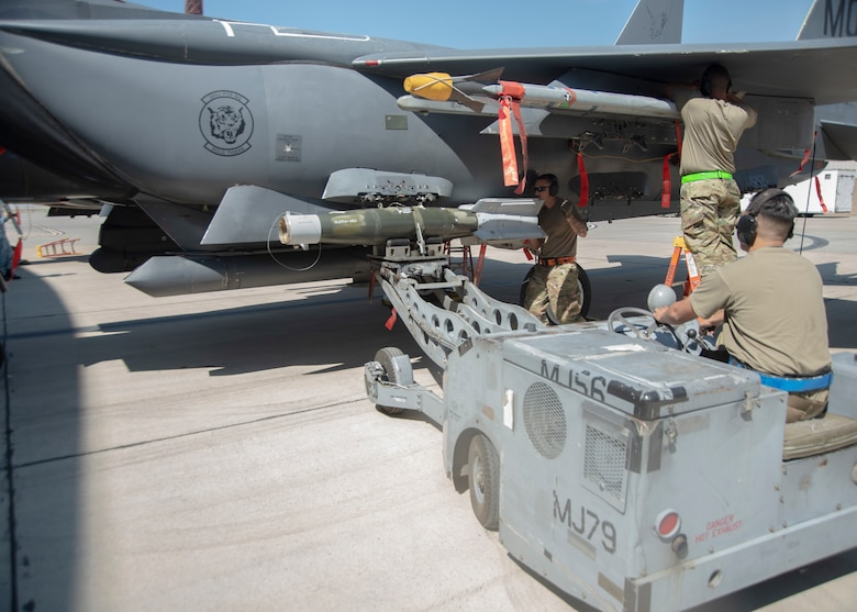Three Airmen work together to load and secure a Guided Bomb Unit-12 and an Air Intercept Missile-9X to a F-15E Strike Eagle.