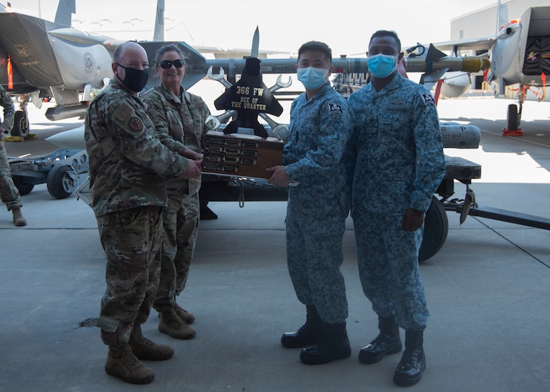 Two Airmen from the United States Air Force and two Airmen from Republic of Singapore pose for a photo with the Dedicated Crew Chief Competition trophy.
