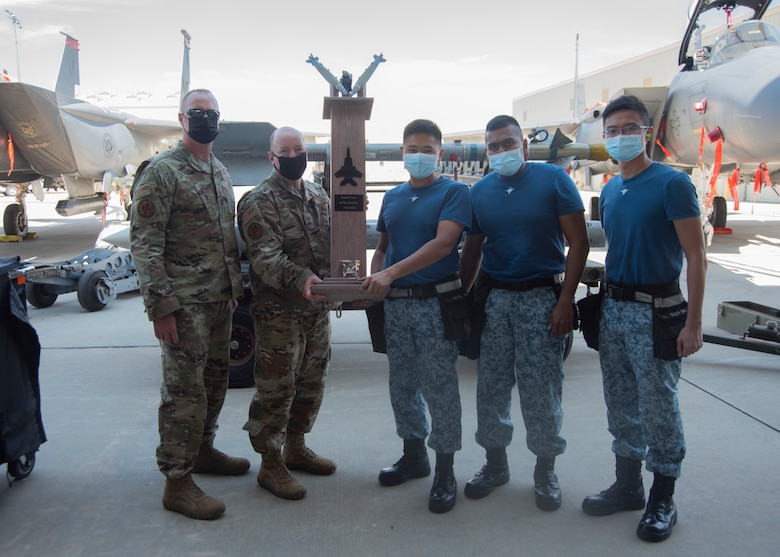 Two Airmen from the United States Air Force and Three Airmen from Republic of Singapore Air Force pose for a photo with the Quarterly Load Crew Competition trophy.