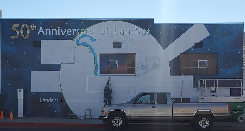 Ann Thompson, City of Lompoc Mural Society curator, sketches the Landsat satellite mural located on Ocean Avenue and I street on June 22, 2021, in Lompoc, California. Thompson was chosen to paint the mural by NASA to celebrate the 50th anniversary of Landsat. (U.S. Space Force photo by Airman First Class Tiarra Sibley)